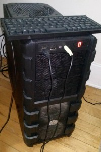 Outside the box with the compact format keyboard and the 2x 120mm fans blowing on the drives visible.